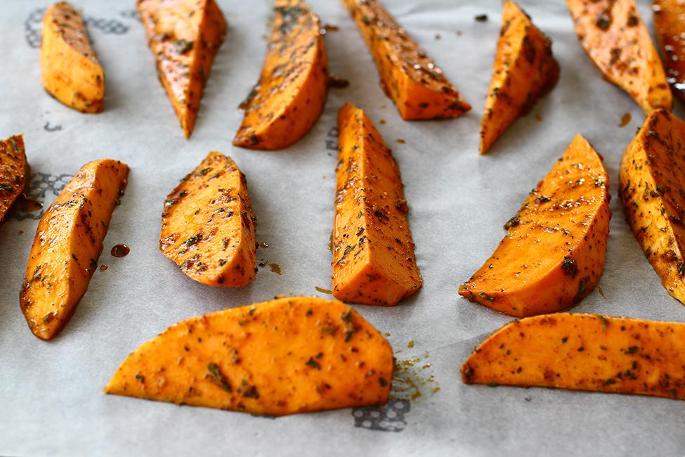 cartofii dulci condimentati aranjati in tava inainte de a ii da la cuptor